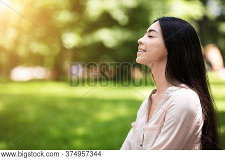 Life Harmony. Portrait Of Relaxed Asian Girl Breathing Deeply With Closed Eyes In Park, Side View Wi