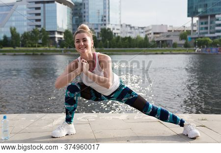 Full Length Shot Of Fit Young Woman Doing Stretching Workout. Fitness Model Exercising In Morning Ou