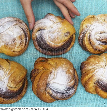 Top View Of Womens Hand Holding A Sweet Bun. There Are More Buns Nearby. Bakery Concept. Space For T