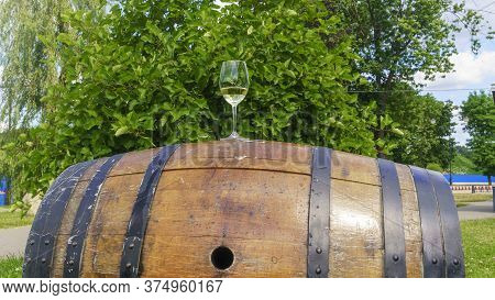 Wineglass Of White Wine Stand On The Wooden Cask On Green Leaves Background. Space For Text. Wine Co