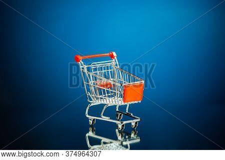 empty shopping cart, blue background