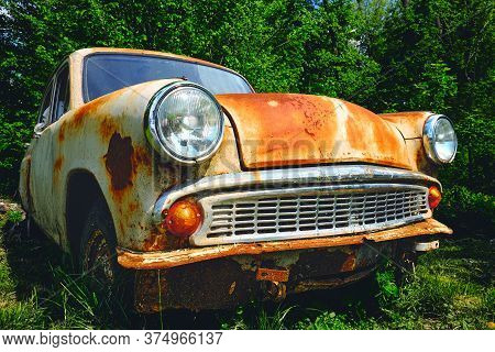 Rusty Old Car Among The Green Bushes In Summer. Car Industry 40s.