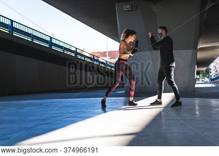 Spanish Woman Training Boxing With Coach Outdoors. Boxing Concept.