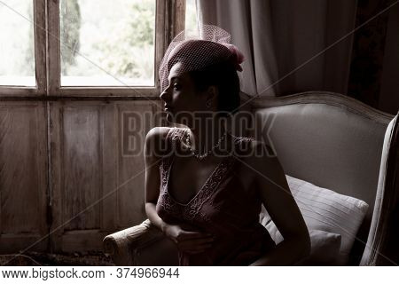 Attractive young woman in 1920s flapper dress sitting in dark room near windows, with clair obscur light effect