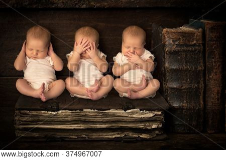 Three sleeping newborn babies doing the hear see speak no evil gestures while sitting on a stack of antique books (no triplets, just 3x same baby).
