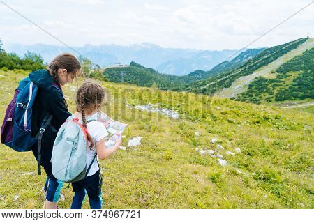Children Hiking On Beautiful Summer Day In Alps Mountains Austria Resting On Rock. Kids Look At Map
