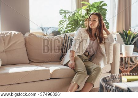Portrait Of Business Woman At Home Sitting On Couch