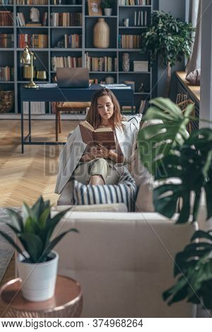 Young Woman At Home Is Lying On The Sofa With Book.
