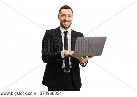 Businessman working on a laptop computer and smiling at the camera isolated on white background
