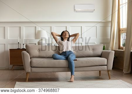 Happy Young Calm Woman Breathing Fresh Cool Air Indoors.