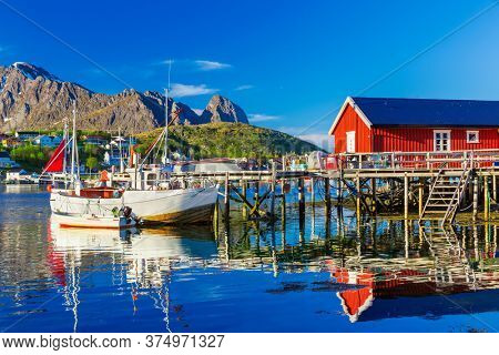 Fishing boats in Reine Village, Lofoten Islands,  Norway.  The Typical Norwegian fishing village of Reine under midnight sun,  with the typical red rorbu houses.  Mountain In Background