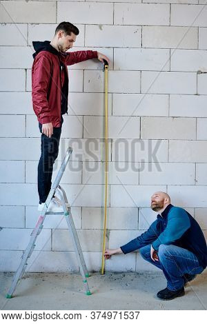 Young builder standing on stepladder and holding measuring tape by brick wall while his colleague sitting on squats and consulting with him