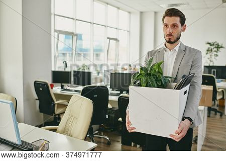 Unhappy young office worker carrying box with green plant, documents and other supplies while leaving his workplace after quarantine