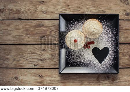 Cupcakes on a plate. Cupcakes on a wooden table. Sweet cupcake with heart for Valentine\'s Day.