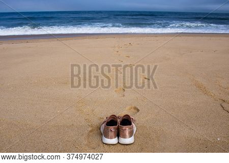 Pink Canvas Shoes Resting On The Sand Facing The Ocean At Empty Beach With Footprints And Waves In T