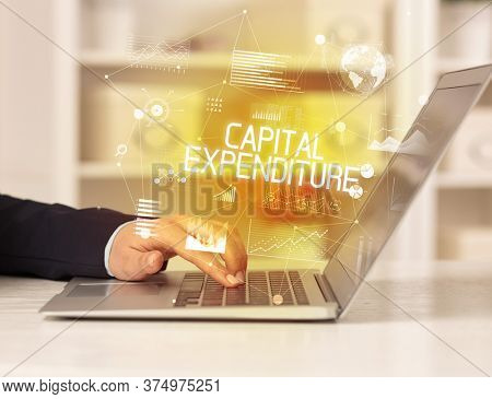 Side view of a business person working on laptop with CAPITAL EXPENDITURE inscription, modern business concept