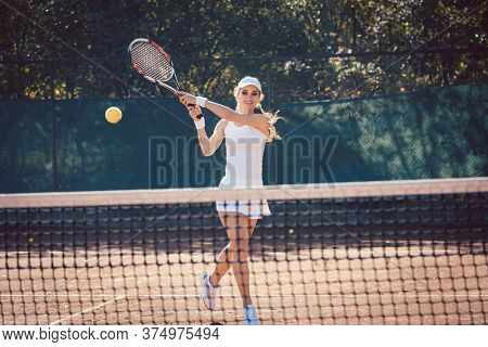 Woman forcefully playing tennis on court