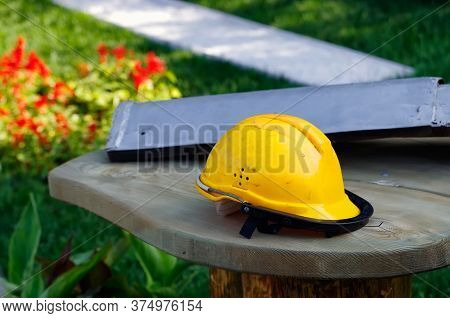 Dirty Orange Workman's Safety Helmet (hard Hat) On Wooden Table