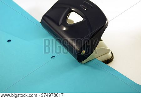Office: Punch, Blue Paper With Punch Holes On A White Background With Place For Text