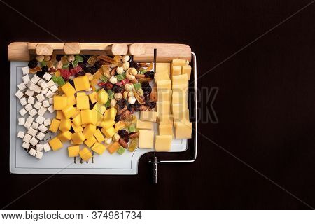 Cheese Dish With Various Cheeses And Dried Fruits On A Sliced Board With Devices For Slicing.special