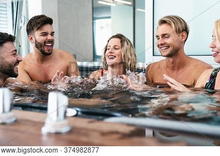Happy Friends Enjoying Vacations In Jacuzzi Luxury House - Young People Having Fun Together In Hot T