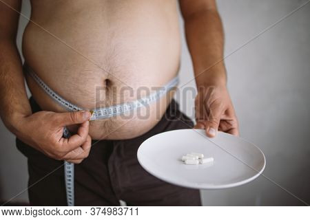 Overweight Man Holding Plate With Slimming Pills. Unhealthy Way To Get Slim. Weight Loss, Dieting, F