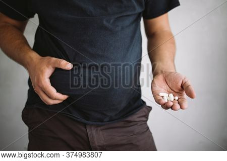 Overweight Man Holding Slimming Pills. Unhealthy Way To Get Slim. Weight Loss, Dieting, Fat Burning,