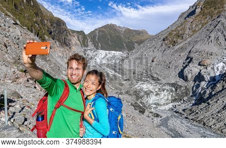 Selfie couple taking phone self-portrait on New Zealand by Franz Josef Glacier. New Zealand tourists smiling happy in nature by Franz Josef Glacier, Westland Tai Poutini National Park.