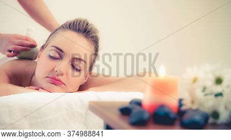 Massage Therapist Holds A Herbal Compress To Do Treatment To Woman Lying On Spa Bed In A Luxury Spa