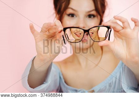 Eccentric Young Woman Holding Glasses In Front Of Her Face, Sticking Tongue Out
