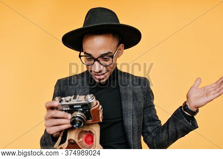 Amazed Black Man In Hat Looking At Camera. Studio Portrait Of Emotional African Male Photographer St