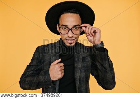 Studio Portrait Of Handsome Brown-eyed Male Model Playfully Touching His Hat. Indoor Photo Of Well-d