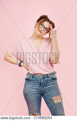 Perky Emotional Girl In Loose Pink Top And Jeans Looks Up