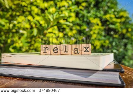 The Word Relax, Letters On Block Cubes On Top Of Books And Wooden Table With Green Trees, Outdoor Na