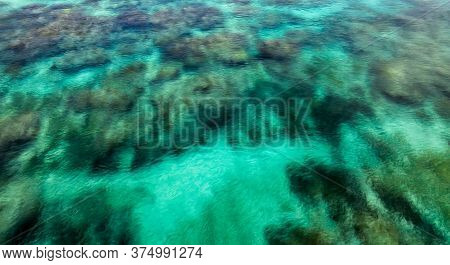 Close Background View Of Crystal Clear Ocean Water With Coral Reefs Underneath It.