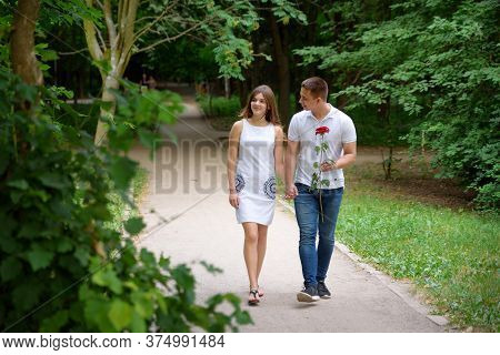 Young Man And Woman Are Walking In The Park Holding Hands