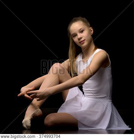 Portrait Of A Beautiful Preteen Girl Sitting On The Floor, Hugging Her Knees, A Charming Girl With B