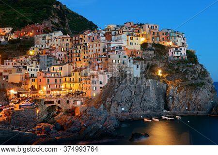 Manarola overlook Mediterranean Sea with buildings over cliff in Cinque Terre at night, Italy.