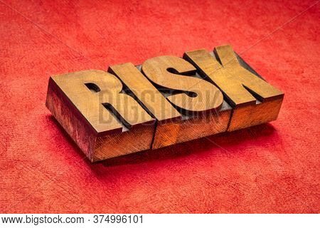 risk word in vintage letterpress wood type against red textured paper, business, danger and uncertainty concept