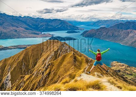 Hiker jumping of joy funny - man hiking in New Zealand. Roys Peak, South Island, New Zealand.
