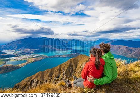 New Zealand hiking couple on mountain top Roys Peak relaxing sitting enjoying active outdoor lifestyle looking at view of amazing New Zealand nature landscape, near Wanaka, Otago, South Island.