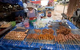KHAO LAK, THAILAND - 29 JUNE 2020: Asian street market with local woman selling traditional barbecue meats and sausages.