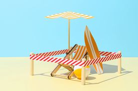 Sunbed With Umbrella, Surfboard And Ball On The Beach. Isolated Vacation Spot At Resort. Minimalisti
