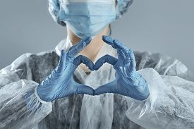 Woman In Medical Mask And Hands In Latex Glove Shows The Symbol Of The Heart.