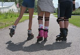 Cropped View Of Teenagers Moving In Roller Skates. Group Of Friends Skating In The Street. Cheerful