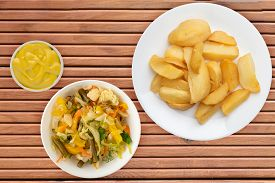 Fry Potatoes With Vegetable Salad On A Orange Wooden Background. Fry Potatoes On A White Plate