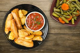 French Fries With Ketchup On Brown Wooden Background. French Fries On Black Plate With Vegetarian Sa