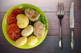 Cutlet With Potatoes On Lime Plate With Fork And Knife Top View. Cutlet With Potatoes On Purple Wood