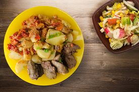 Fried Liver With Potatoes And Stewed Tomatoes With Vegetarian Salad. Fried Liver On Yellow Plate On