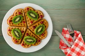 Wafers With Kiwi And Cranberries On A Green Wooden Background. Waffles On A White Plate With Fork An
